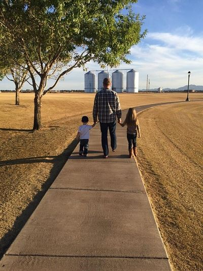 A Father and His Children Walk Hand in Hand down a Winding Park Sidewalk