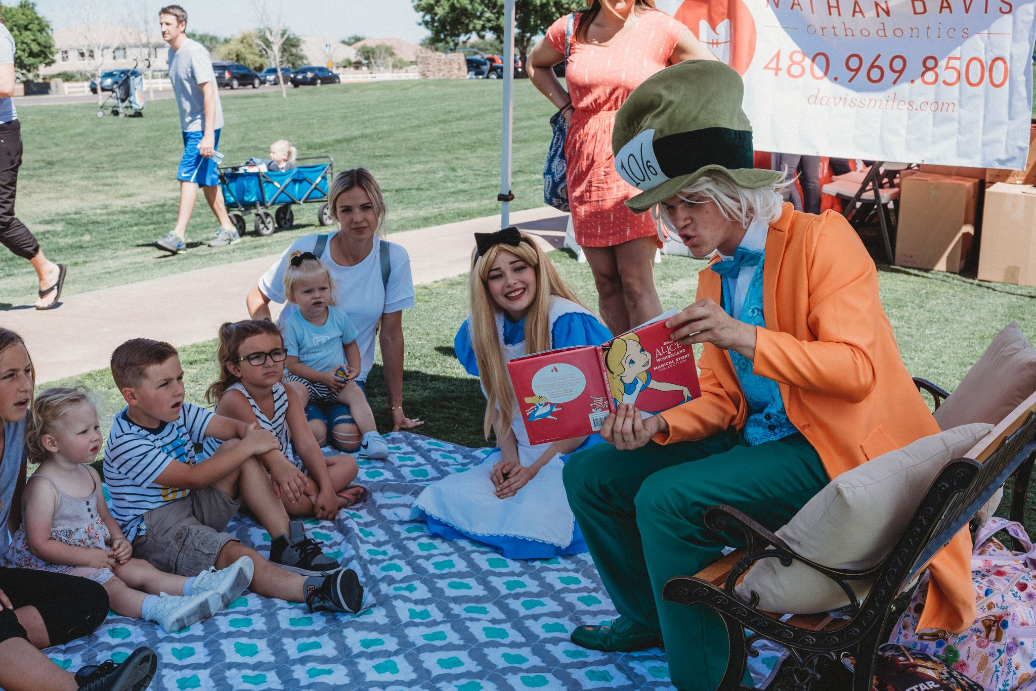 People Dressed as the Mad-Hatter and Alice from Alice and Wonderland Read to Children 4