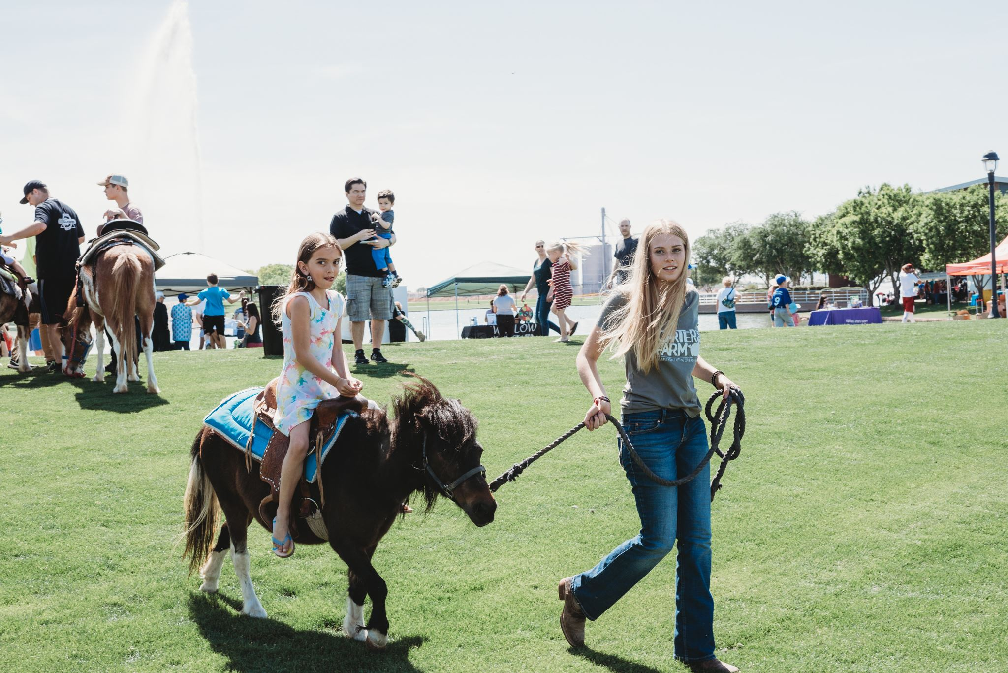Young Girl Riding a Brown Pony Being Led by an Assistant 2