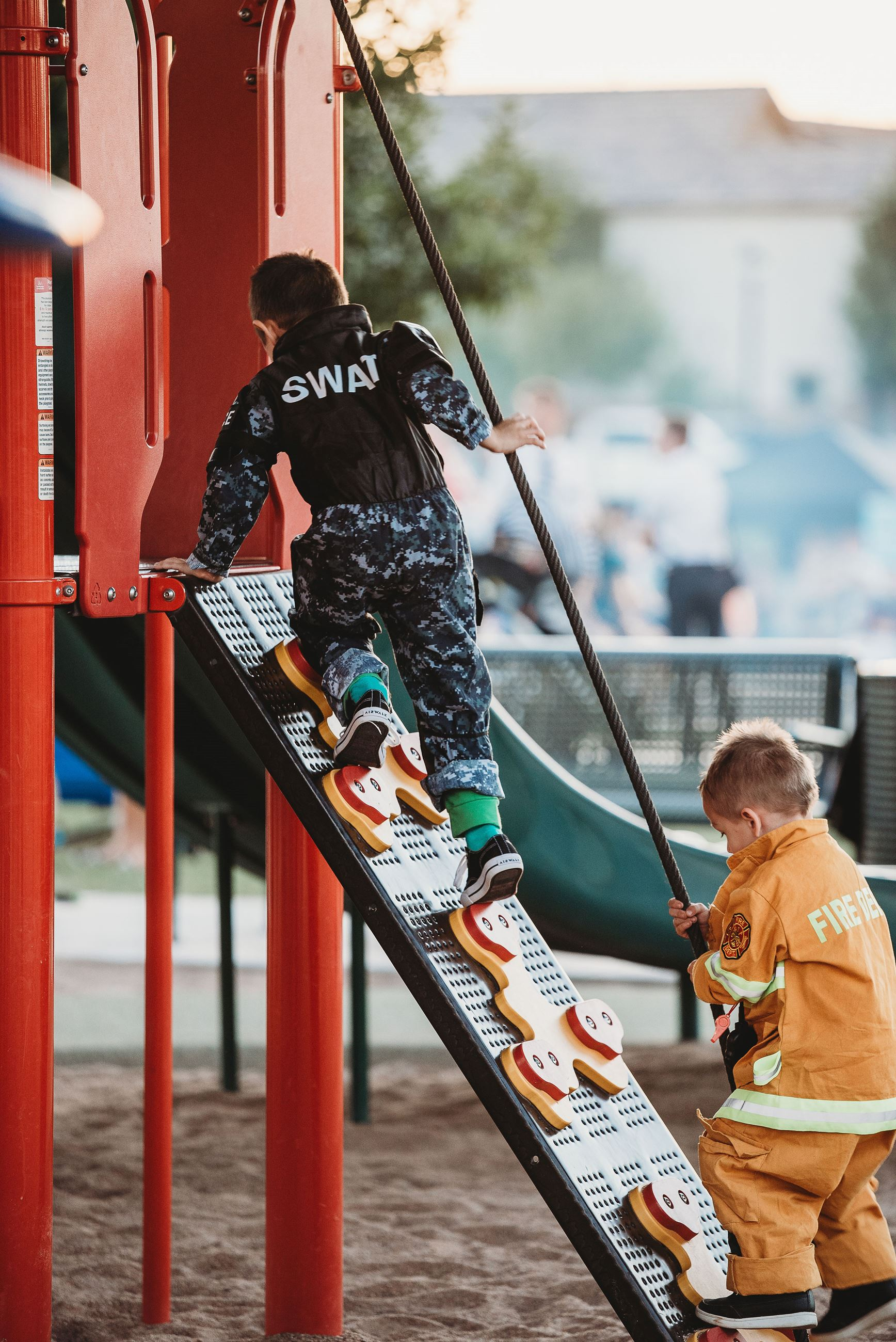 Two Young Boys Dressed as a SWAT Team Soldier and a Firefirefighter Climb a Play Structure