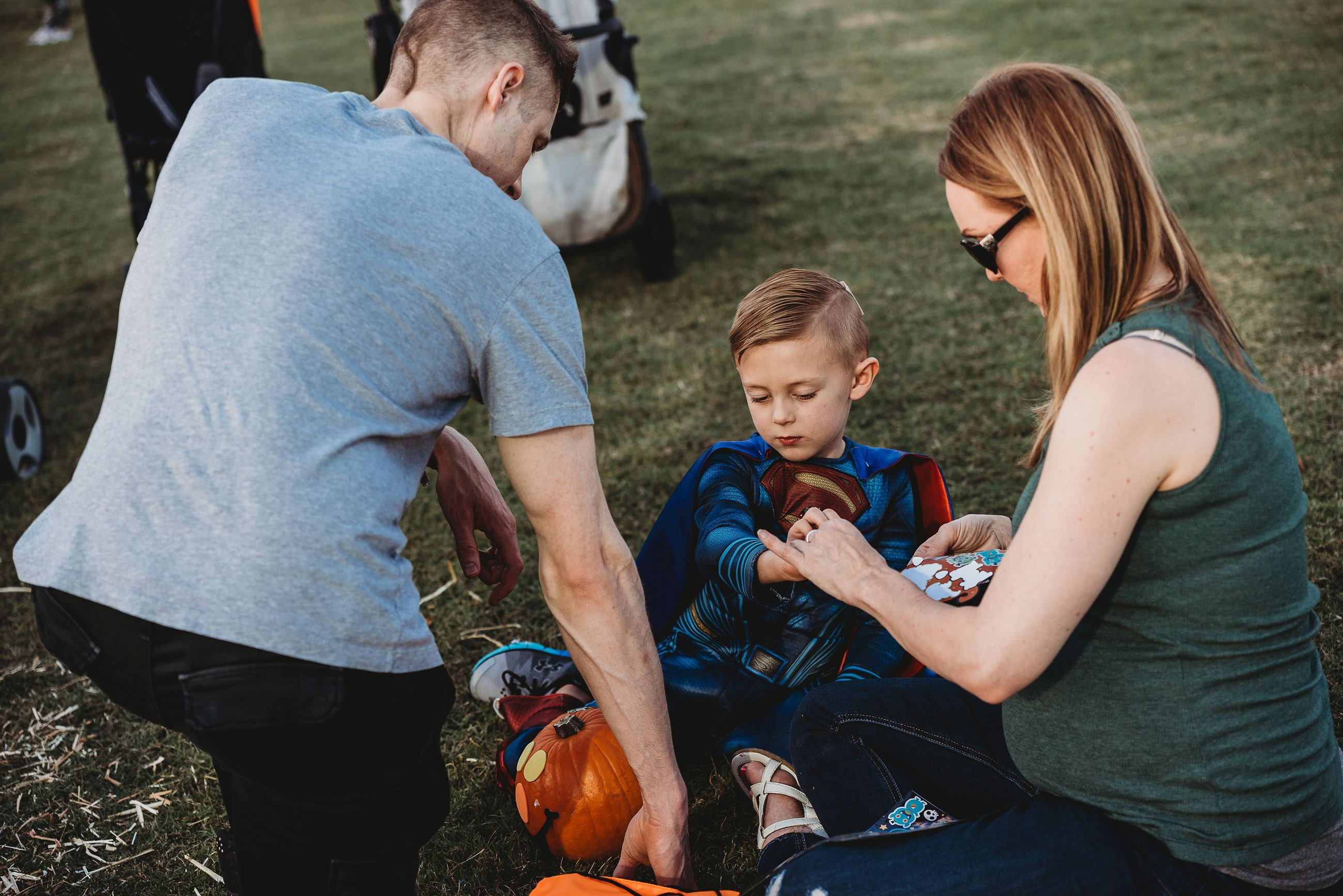 Young Boy Dressed as Superman Paints Pumpkins with His Parents