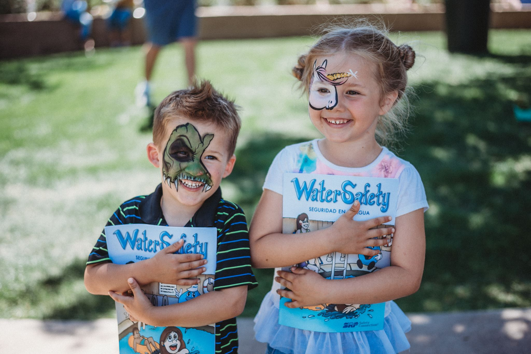 Two Kids Wearing Face Paint and Holding Water Safety Booklets