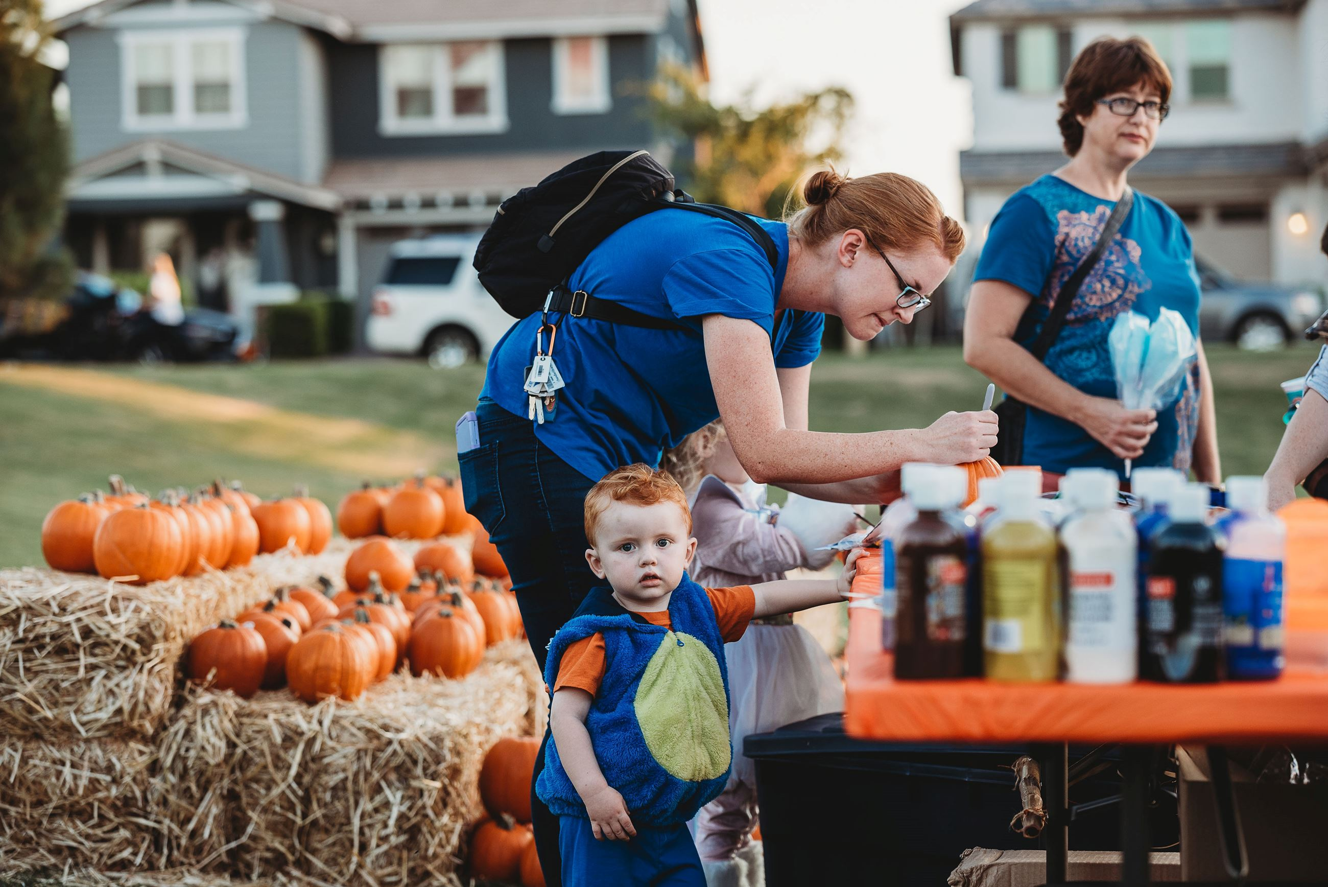 A Focused Mother Paints a Pumpkin While Her Toddler Son Notices the Camera