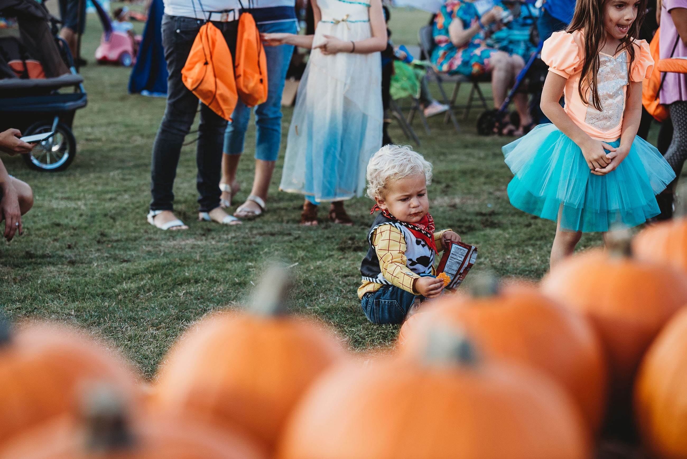 Baby Dressed as Woody from Toy Story Sits in the Grass Next to a Bunch of Pumpkins