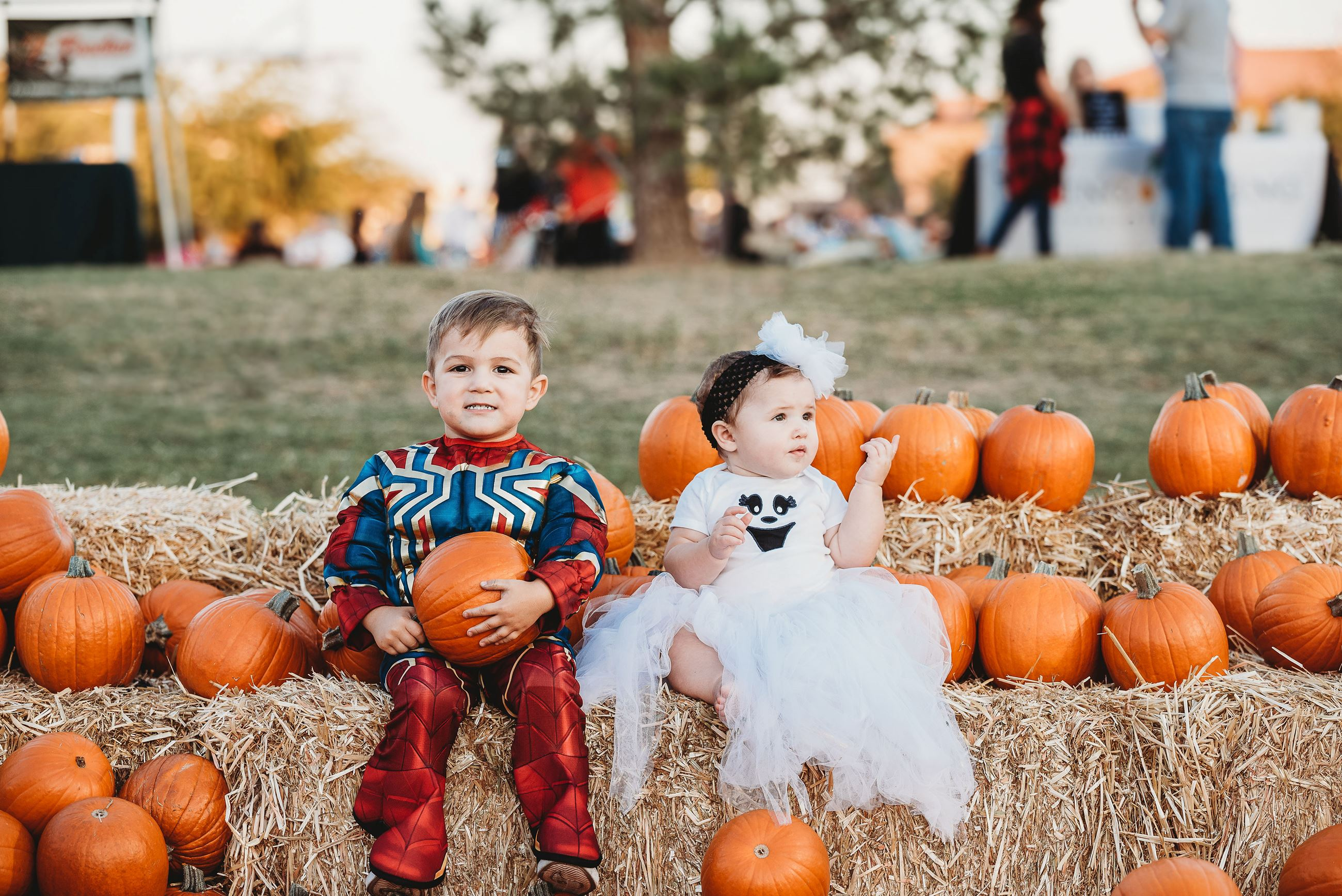 Boy Dressed as Spiderman, and His Sister as a Ghost, Sit on Hay Bales Between Lots of Pumpkins