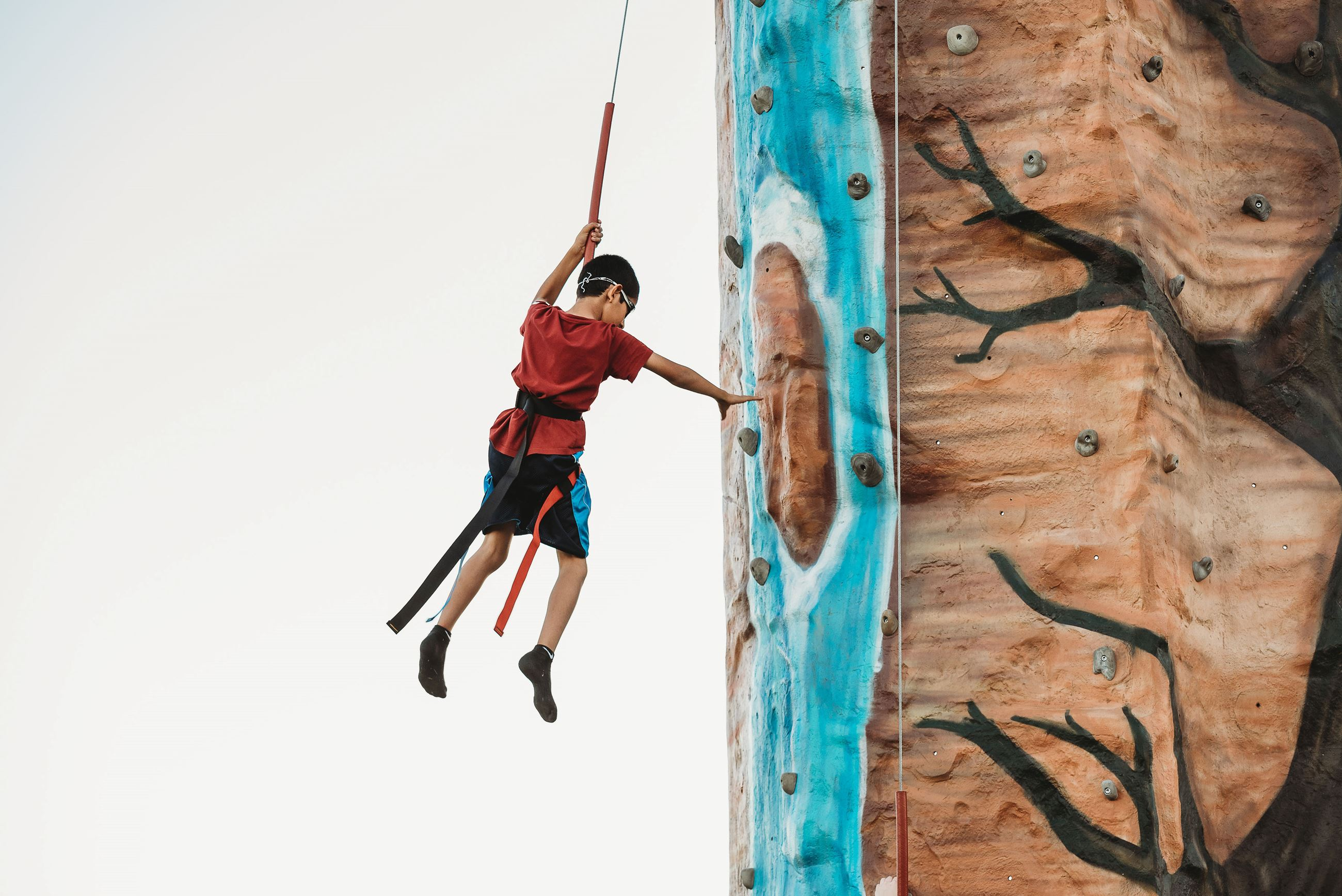 Boy in a Red Shirt Carefully Hops down a Rock Climbing Wall