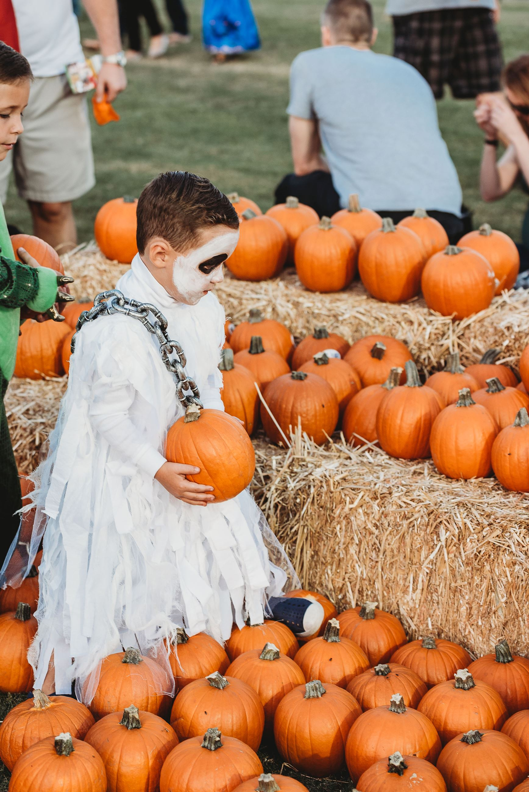Boy Wearing Ghostly Face Paint Holds a Pumpkin