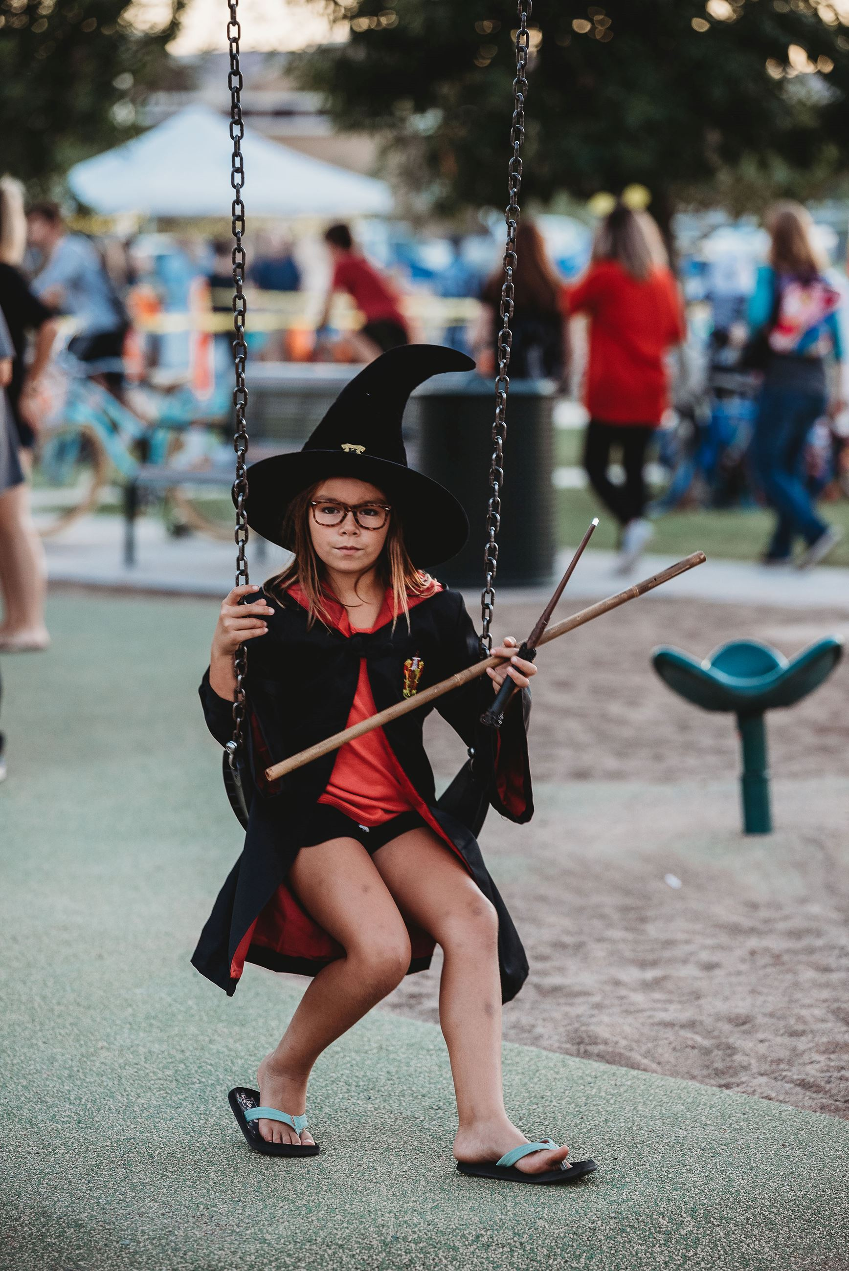Girl Dressed as a Witch Sitting on a Swing