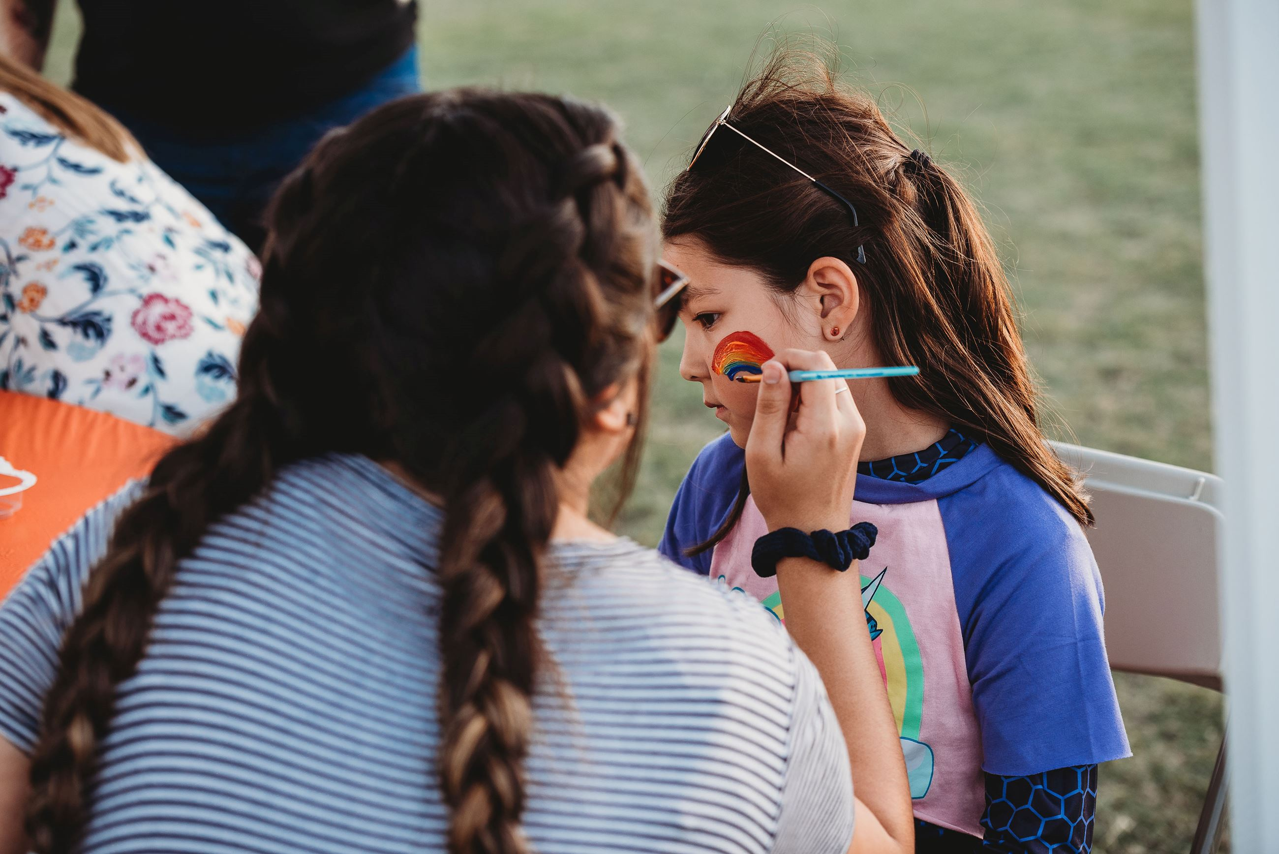 Girl Getting a Rainbow Painted on Her Cheek
