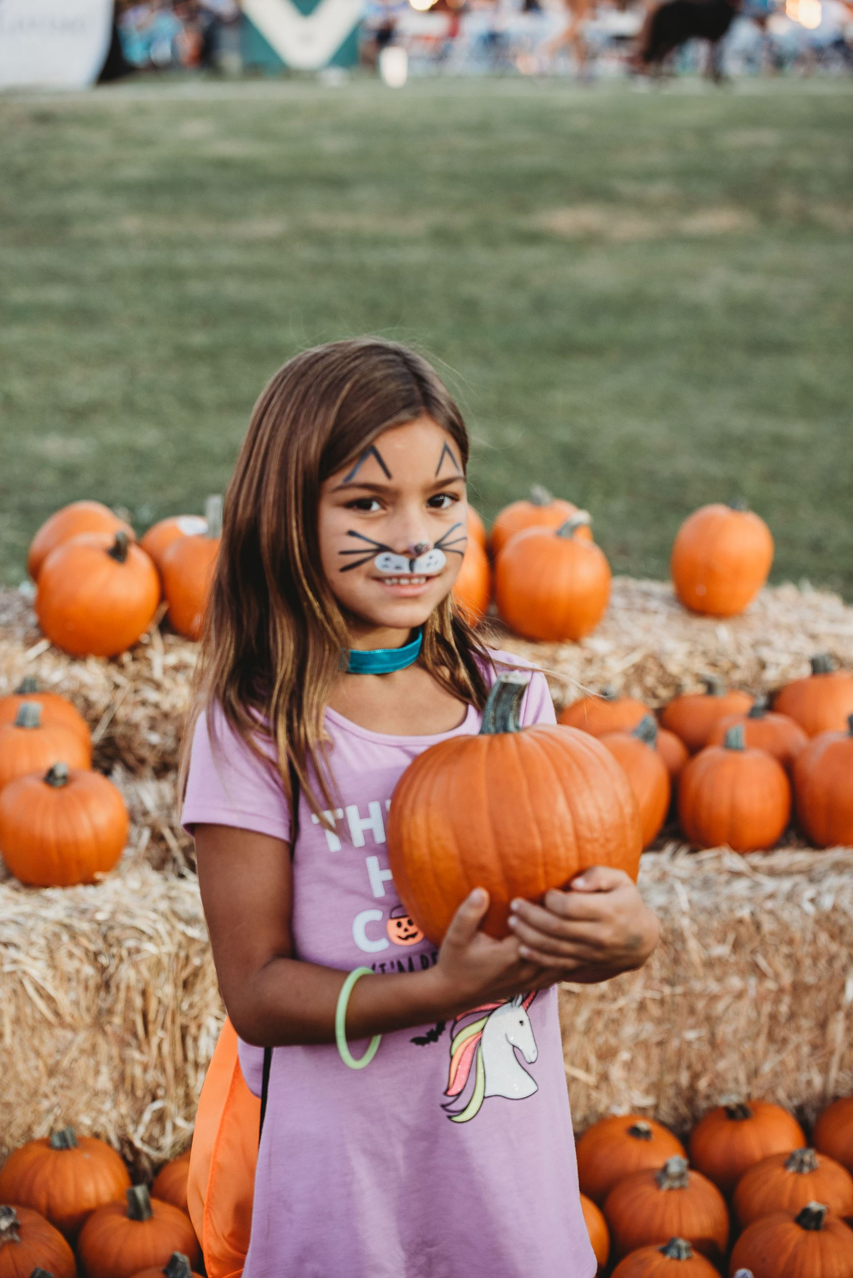 Girl Wearing Cat Face Paint Holds a Pumpkin