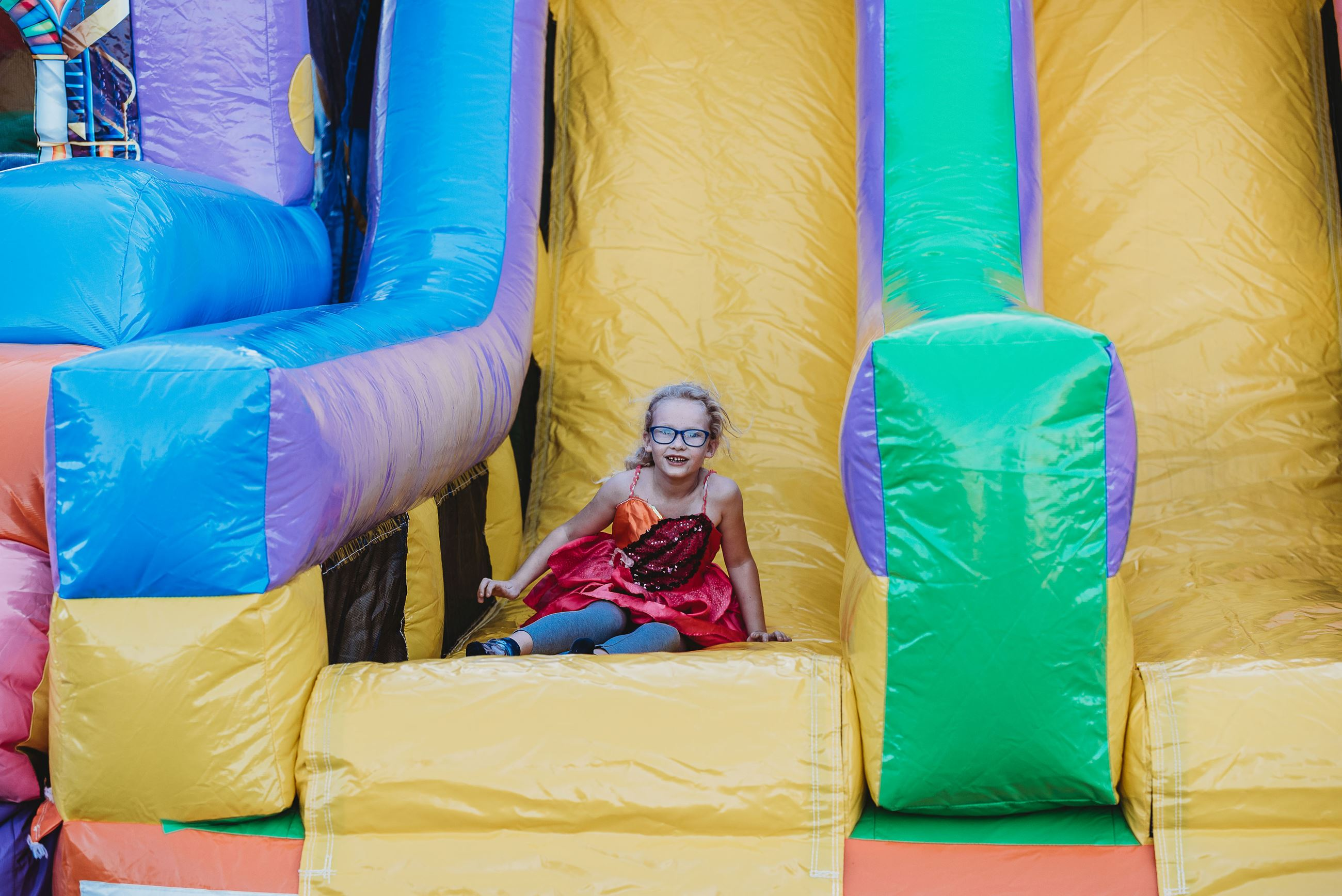 Little Girl Reaches the Bottom of an Inflatable Slide