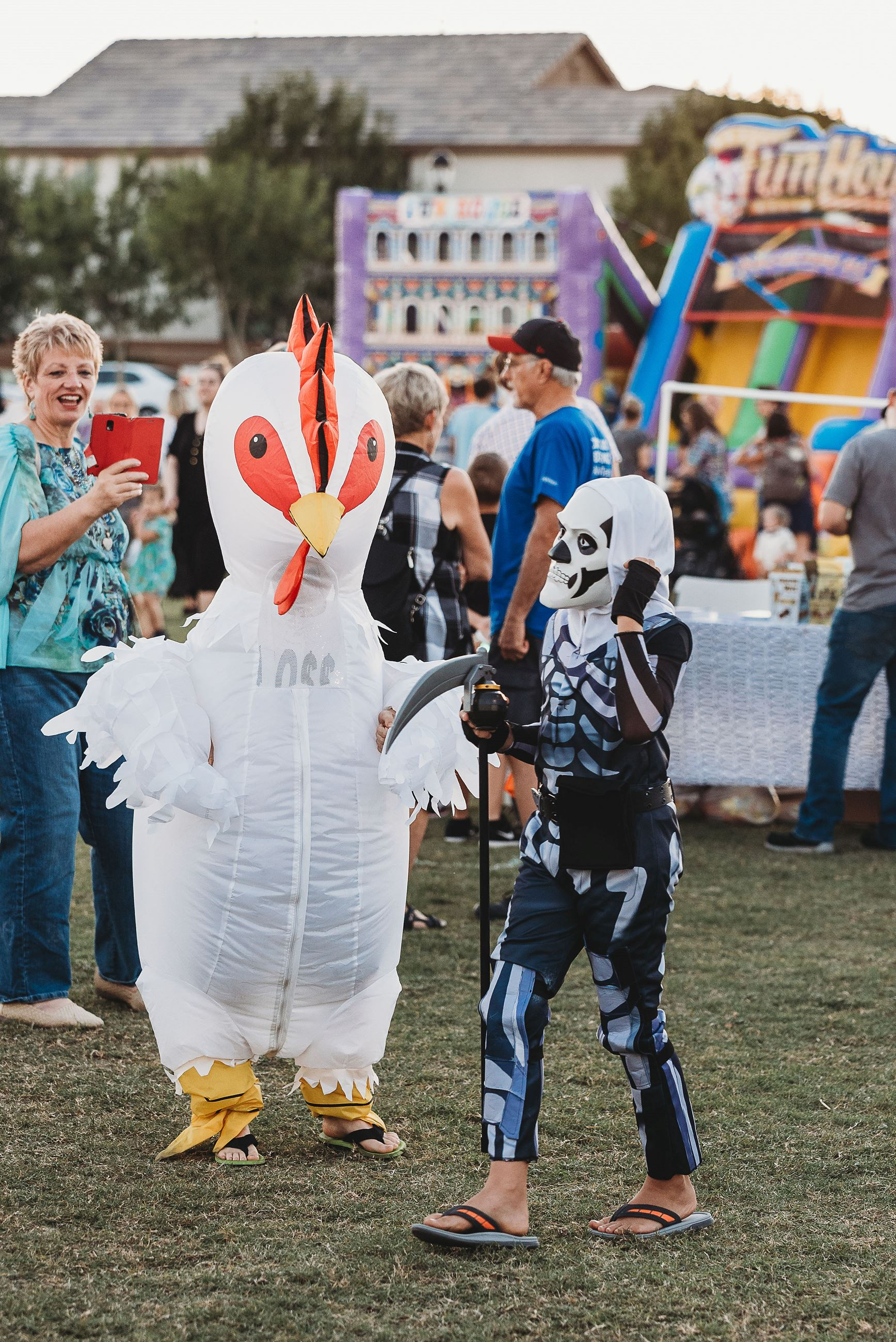 Person in an Inflatable Chicken Suit Next to Someone Dressed as a Skeleton