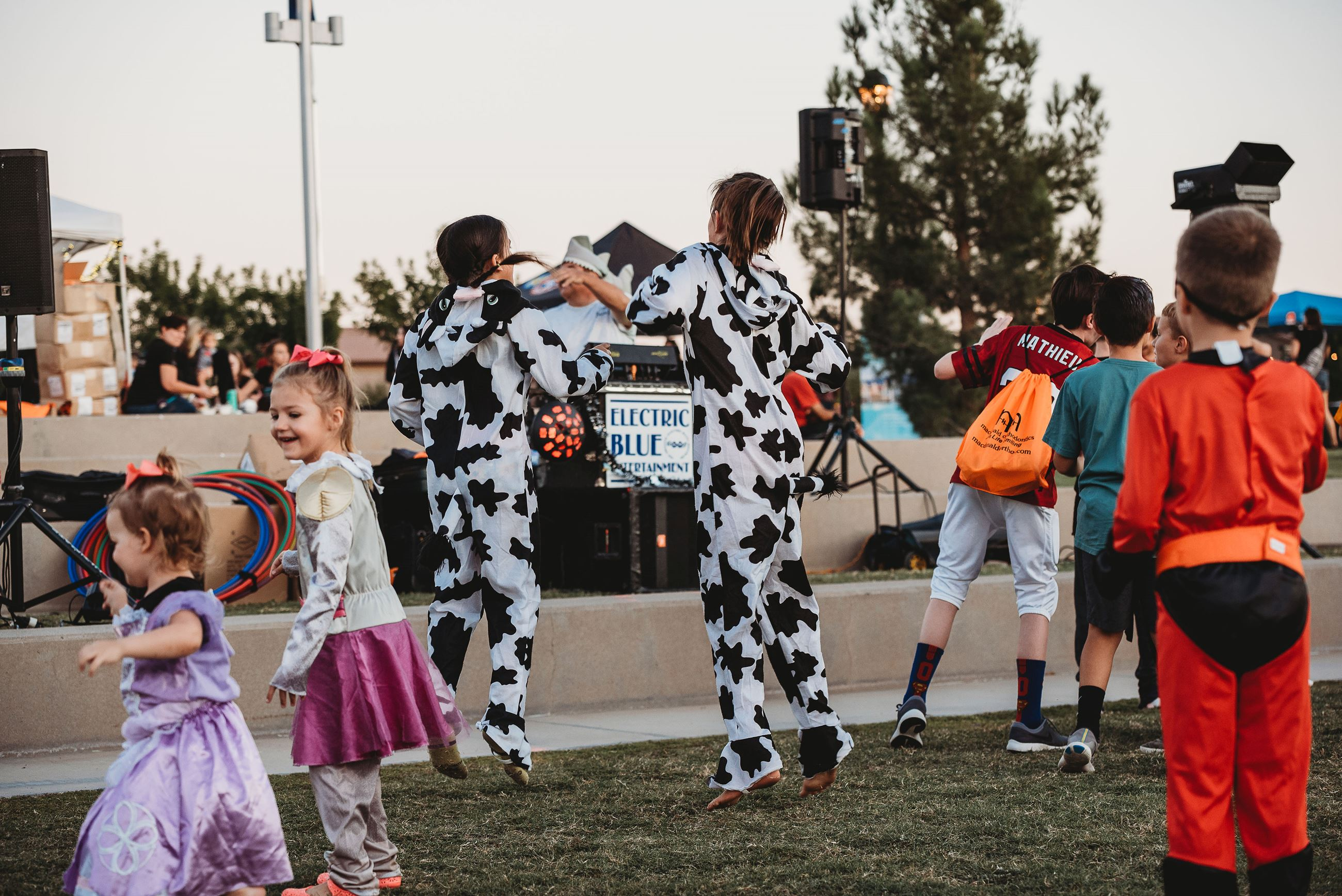 Two People Wearing Cow Onsies Jump Together at a Dance Scene