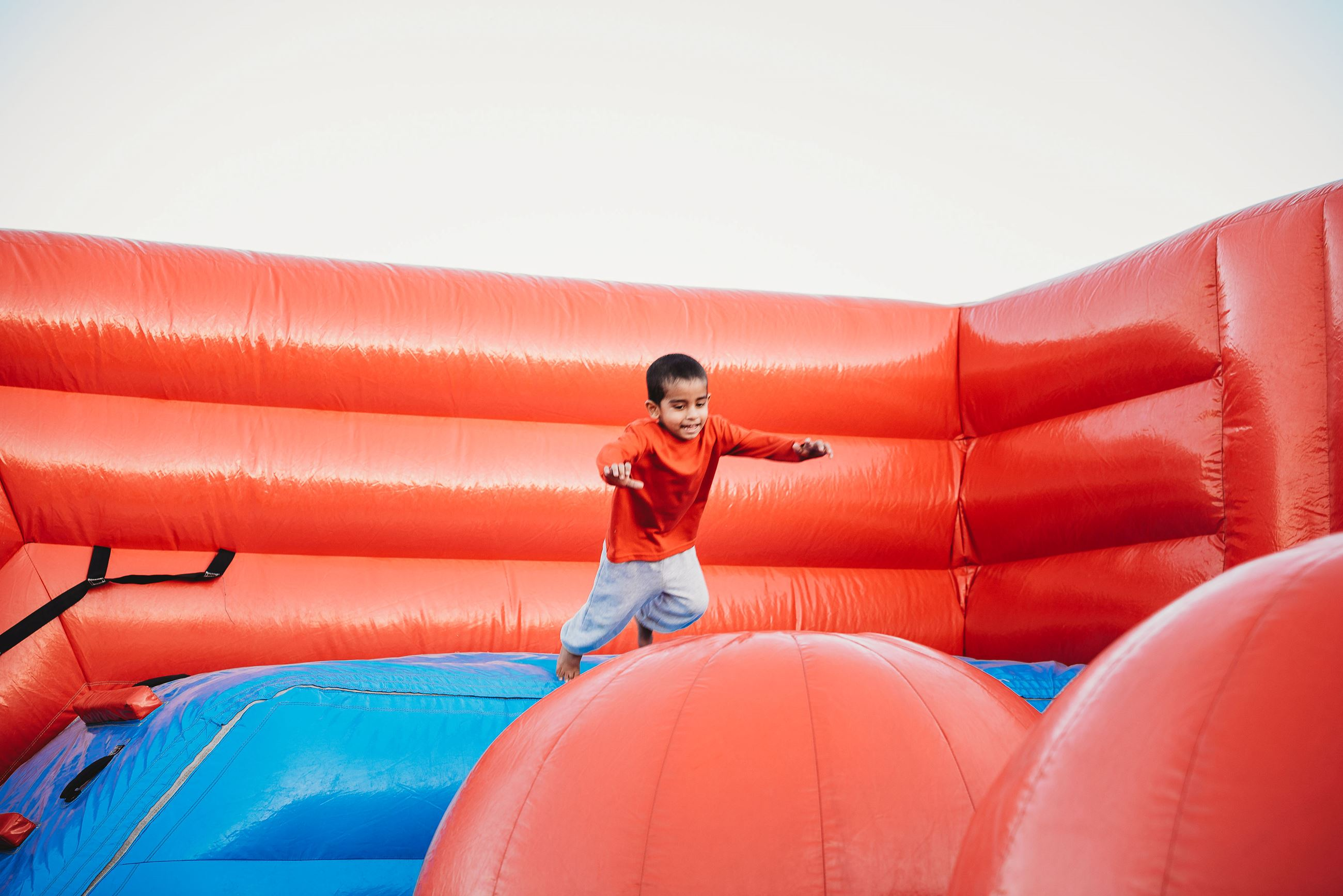 Young Boy in a Red Shirt Participating in a Wipeout Obstacle Course